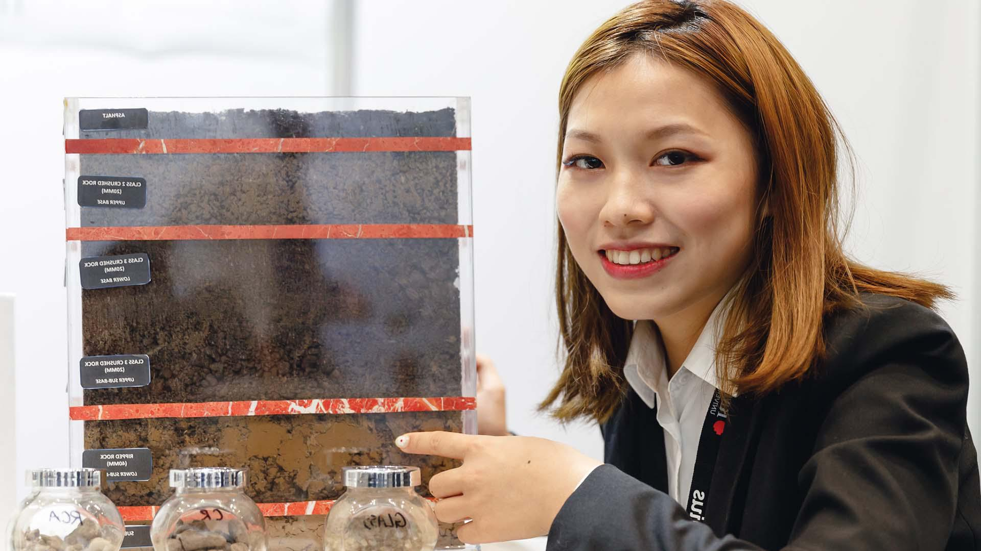 Female student in business clothes showing  display of soil layers