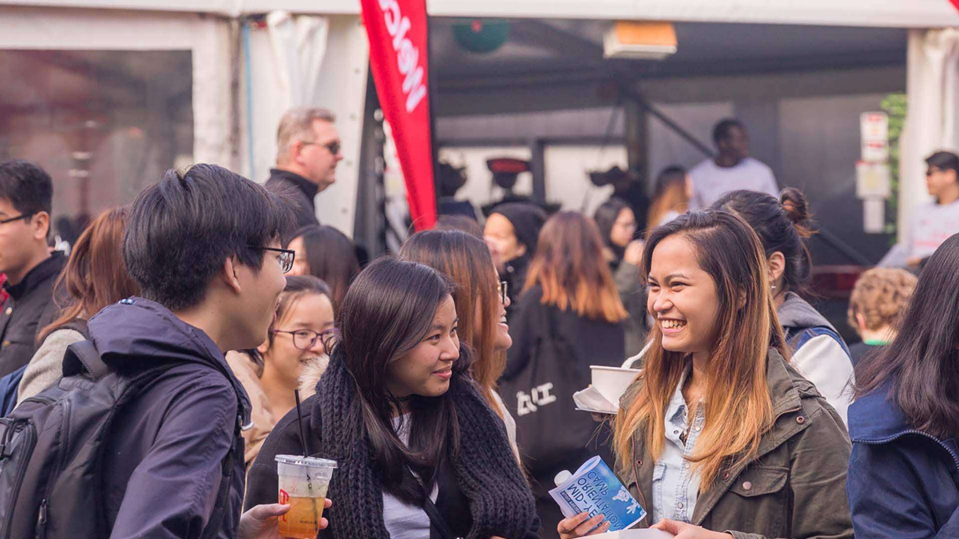 Group of international students talking to each other at Open Day event