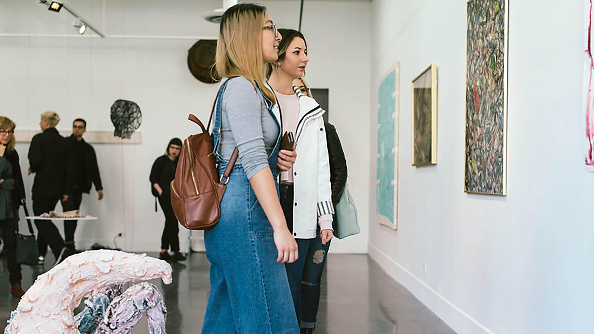 Two women looking at art in gallery space