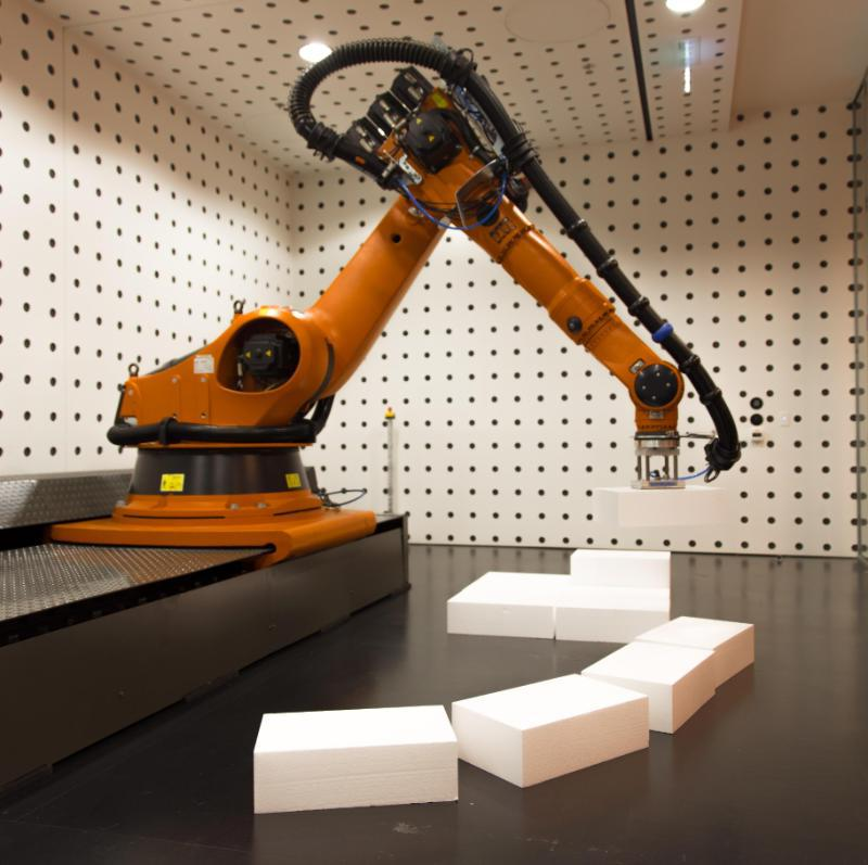 A robotic armed machine moving large rectangles